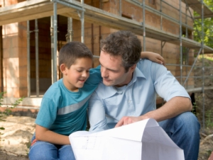Father and son (6-8) looking at blueprint by house under construction